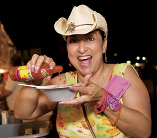woman eats hot sauce at Texas Folklife Festival